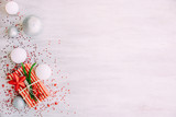 Christmas background with confetti, christmas balls, and red gift boxes on the white wooden board - 237451330
