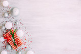Christmas background with confetti, christmas balls, and red gift boxes on the white wooden board - 237451389