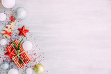 Christmas background with confetti, christmas balls, and red gift boxes on the white wooden board - 237451501