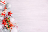 Christmas background with confetti, christmas balls, and red gift boxes on the white wooden board - 237451541