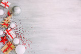 Christmas background with confetti, christmas balls, and red gift boxes on the white wooden board - 237451599