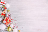 Christmas background with confetti, christmas balls, and red gift boxes on the white wooden board - 237451701