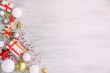 Christmas background with confetti, christmas balls, and red gift boxes on the white wooden board - 237451759