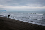 Surfing on the black volcanic beach of the Pacific Ocean, Kamchatka, Russia, the Far East. Extreme sport in cold water.