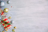 Christmas background with confetti, christmas balls, and red gift boxes on the white wooden board - 237457169
