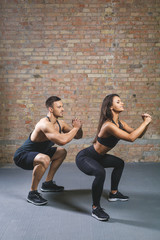 Close up of focused and motivated strong young fitness couple in sportswear crouching and doing squats in the gym.
