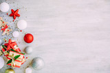 Christmas background with confetti, christmas balls, and red gift boxes on the white wooden board - 237457949