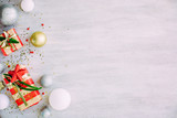Christmas background with confetti, christmas balls, and red gift boxes on the white wooden board - 237458153