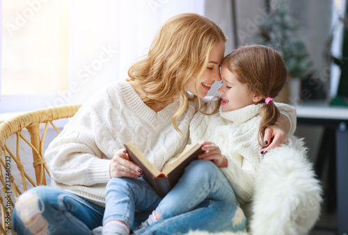 Leinwandbild Motiv happy family mother reads book to child to daughter by window
