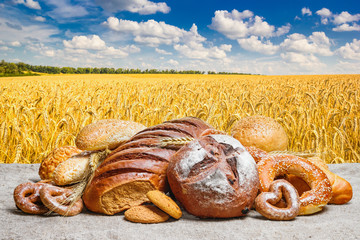 Fresh bread and bakery on sackcloth against the background wheat field with cloudy sky, with space for text