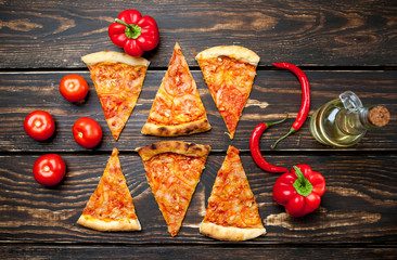 pizza on a wooden table with ingredients, tomato, pepper, sunflower oil