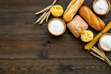 Homemade fresh bread and pasta near flour in bowl and wheat ears on dark wooden background top view space for text