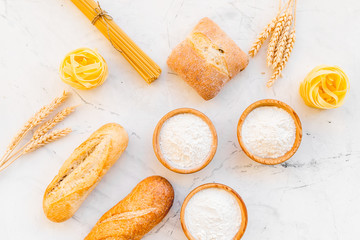Homemade fresh bread and pasta near flour in bowl and wheat ears on white stone background top view
