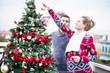 Young couple decorating Christmas tree on balcony