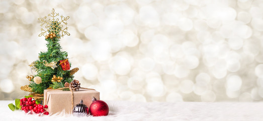 Christmas tree and gift box at blur bokeh light background,Winter holiday banner greeting card.