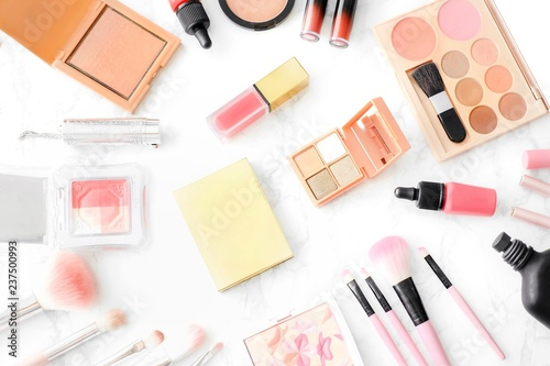 Cosmetics Composition. Pink brush set, lipstick, blush on and eyeshadow palette on marble table. Cosmetic table for women make up concept. Cosmetic products. Flat lay, top view. Copy space. - 237500993