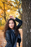 Pretty woman posing with maple's leaves in autumn park near big tree. Beautiful landscape at fall season. - 237502765