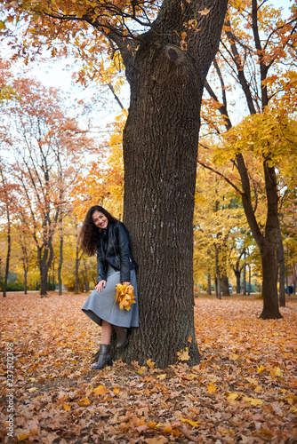 fototapeta na ścianę Pretty woman posing with maple's leaves in autumn park near big tree. Beautiful landscape at fall season.