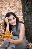 Pretty woman is sitting in autumn park near big tree. Beautiful landscape at fall season. - 237502952