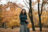 Pretty woman posing with maple's leaf in autumn park near big tree. Beautiful landscape at fall season. - 237502959