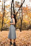 Pretty woman posing with maple's leaf in autumn park near big tree. Beautiful landscape at fall season. - 237502974