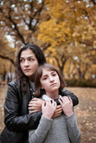 Portrait of pretty woman and teen girl. They are posing in autumn park. Beautiful landscape at fall season. - 237502989