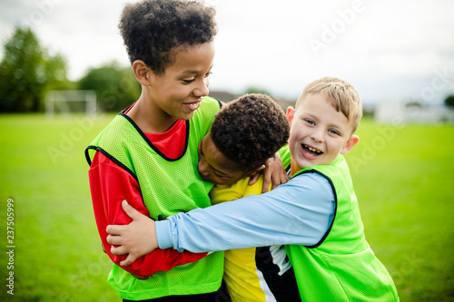 Leinwanddruck Bild Junior football team hugging each other