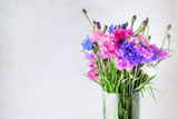 A beautiful bouquet of colorful cornflowers in a glass vase on a light background with copy space.