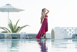 attractive girl in red dress posing near the pool.
