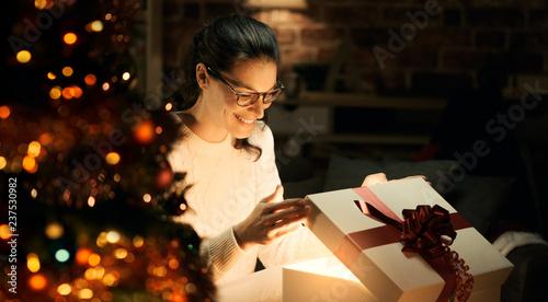 Leinwandbild Motiv Woman opening a magical Christmas gift