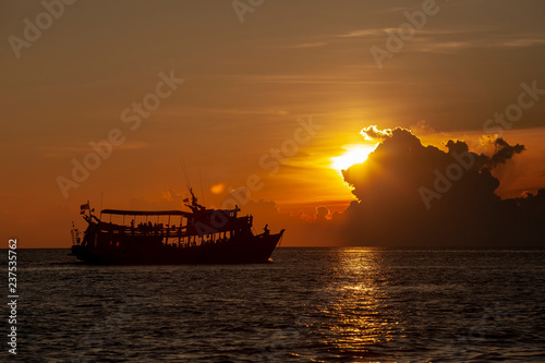tourist scuba diving boat floating at koh tao harbor one of most popular traveling destinaiton in southern of thailand against beautiful sunset sky