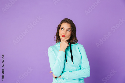 Leinwanddruck Bild Thoughtful young woman posing isolated over purple background wall.