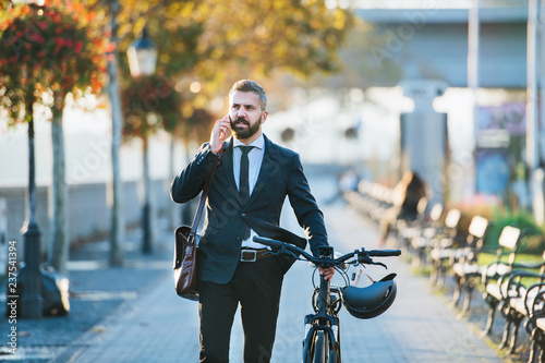Leinwanddruck Bild Businessman commuter with bicycle walking home from work in city, using smartphone.