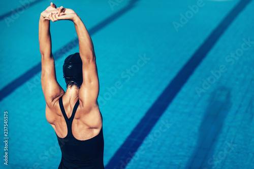 Female warming up on pool edge - 237545575