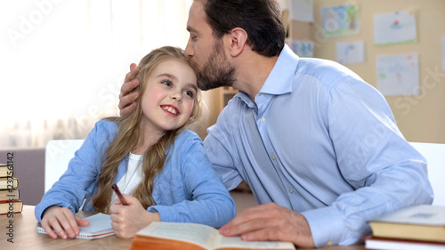 Leinwanddruck Bild Proud father doing homework together with his daughter, education, family care