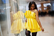 Stylish african american woman at yellow dreess posed at mall.