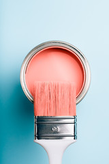 Brush with white handle on open can of Living Coral paint on blue pastel background. Color of the year 2019. Main trend concept.