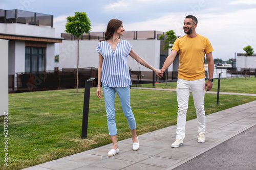 Joyous lady holding hands with her boyfriend and walking forward. They looking at each other with smile. Copy space on left side