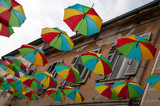 Looking up at colorful umbrellas hanging from the sky between buildings in Pula, Croatia, Europe