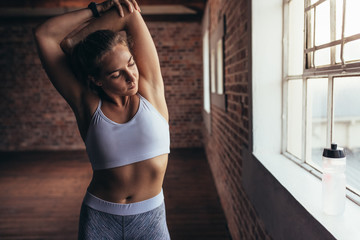 Female warming up for workout at gym