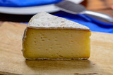 Piece of French Tomme cheese, produced in French Alps and in Switzerland close up