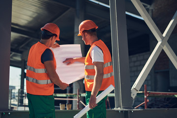 Calm professional builder in green and orange uniform standing outdoors next to his colleague and pointing to the drawing in his hands © YakobchukOlena