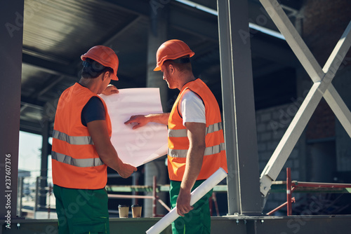 Foto Murales Calm professional builder in green and orange uniform standing outdoors next to his colleague and pointing to the drawing in his hands