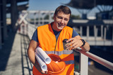 Confident positive young builder wearing an orange vest and smiling while standing alone with coffee and schemes