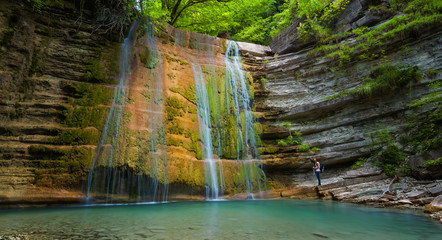 Woman and waterfall in mountain of Caucasus. Summer landscape with waterfall and woman in forest of Caucasus mountain.