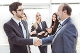 welcome and handshake of business partners on the background of applauding employees