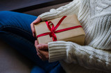 Woman holding in hands christmas present with red ribbon. Xmas concept. Eye bird view.