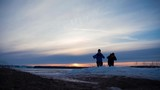 Two men tourist with backpacks are in the mountains in the winter against snow covered. Two friends travel together in picturesque places. Front view, silhouette of people leaving at sunset. - 237645513