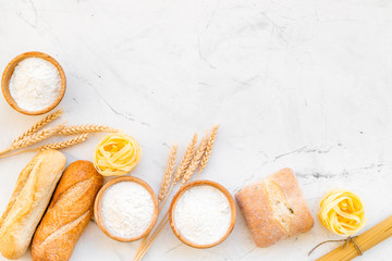 Homemade fresh bread and pasta near flour in bowl and wheat ears on white stone background top view space for text