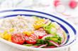 Leinwandbild Motiv Oatmeal porridge with vegetable salad of fresh tomatoes, corn, cucumber and lettuce. Light, healthy and tasty dietary breakfast. Top view